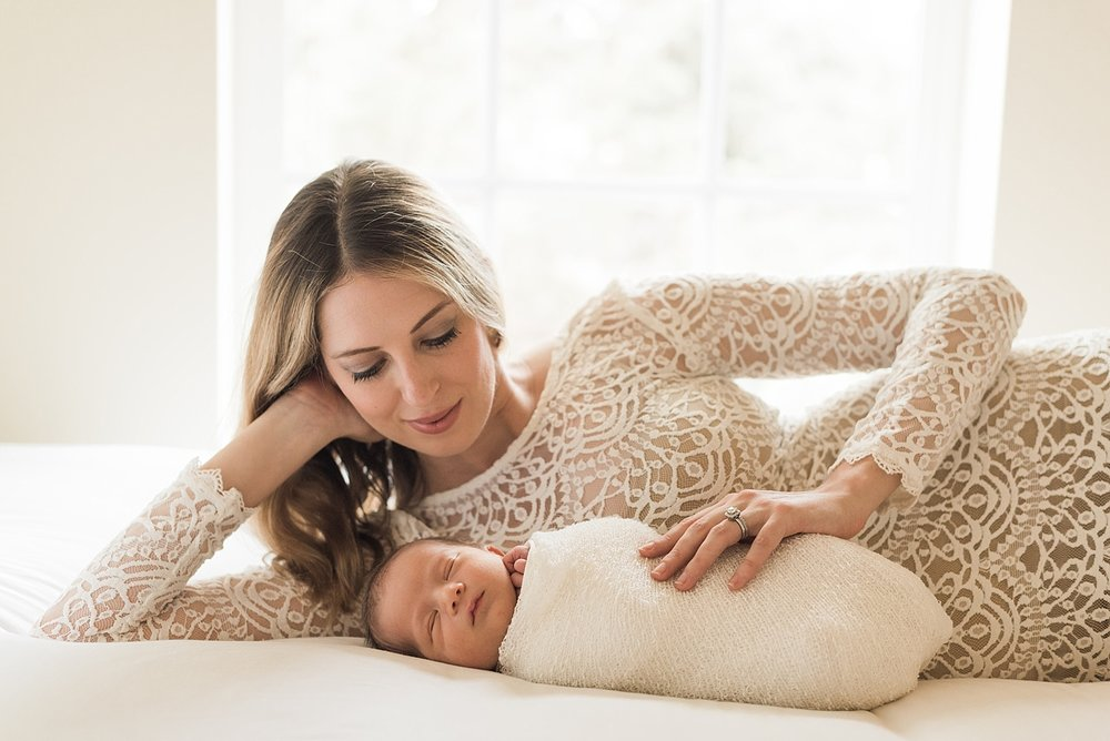 Mom in a gorgeous gown lays on bed with her baby boy