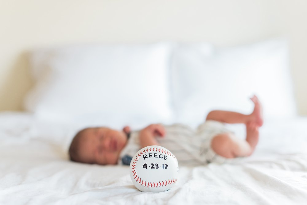 baby boy lays on bed with a baseball