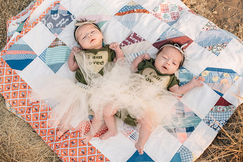 twin baby girls lay on a vintage quilt at smith rock, oregon