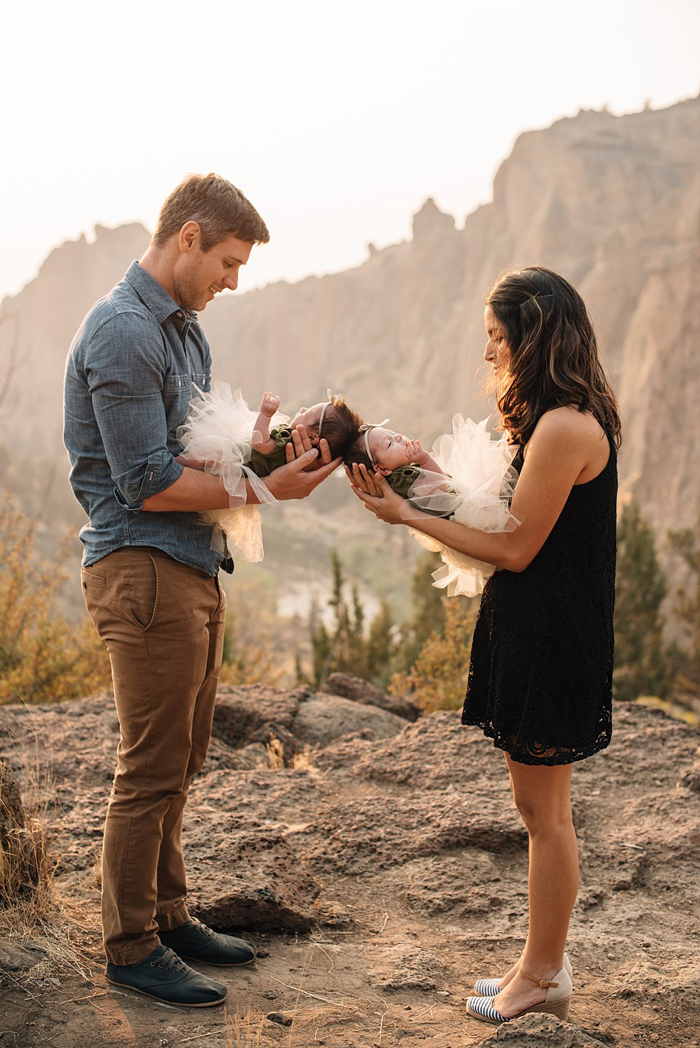 mom and dad hold their newborn girls at smith rock in bend, oregon