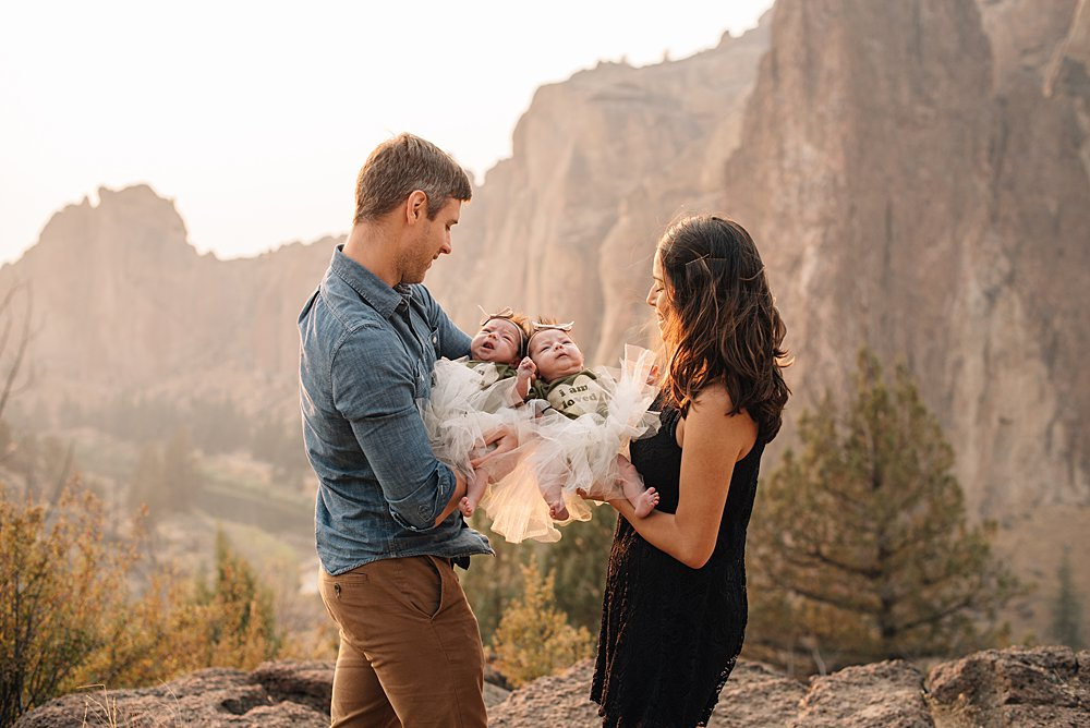 mom and dad look on lovingly at their baby twin girls at Smith Rock, Oregon