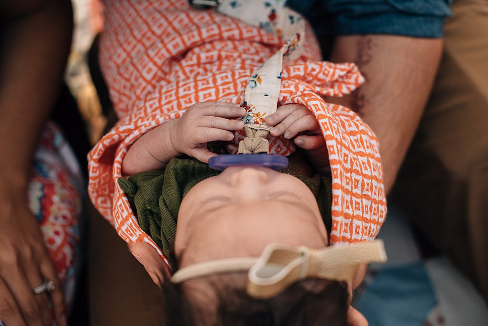 close up of a baby girl sucking a pacifier being held by her dad