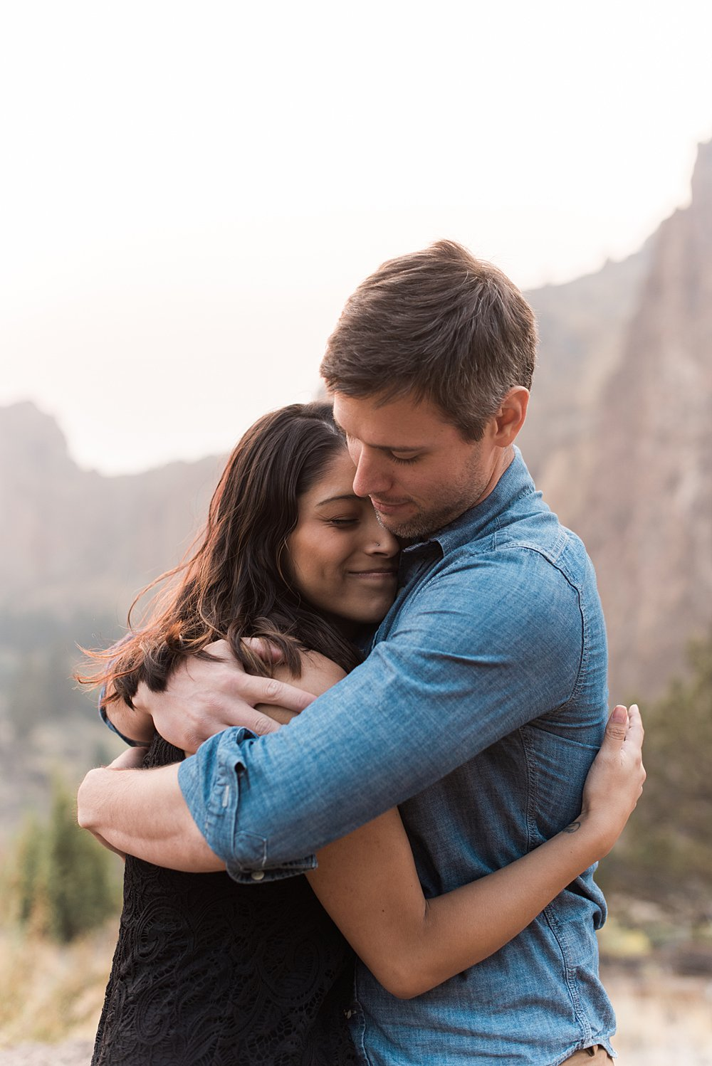 A husband and wife lovingly hug each other with Smith Rock, Oregon as a backdrop.