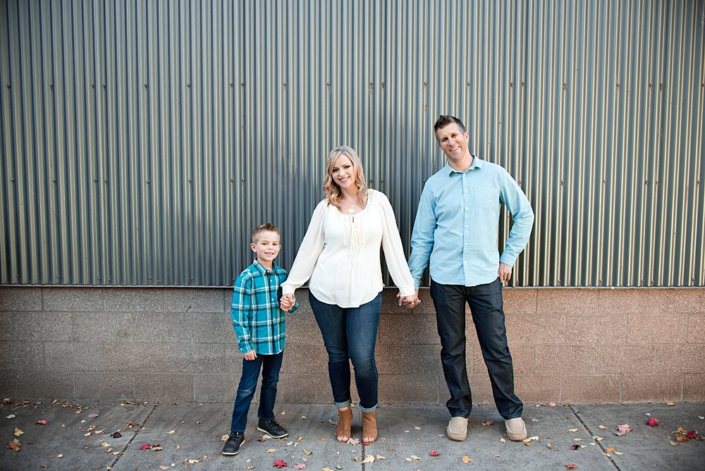 Family poses in front of an urban style building while holind hands in Bend Oregon
