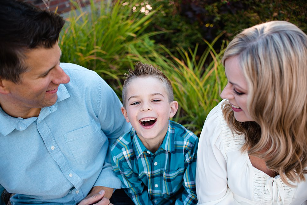 a boy looks up at the camera laughing while his mom and dad tickle him