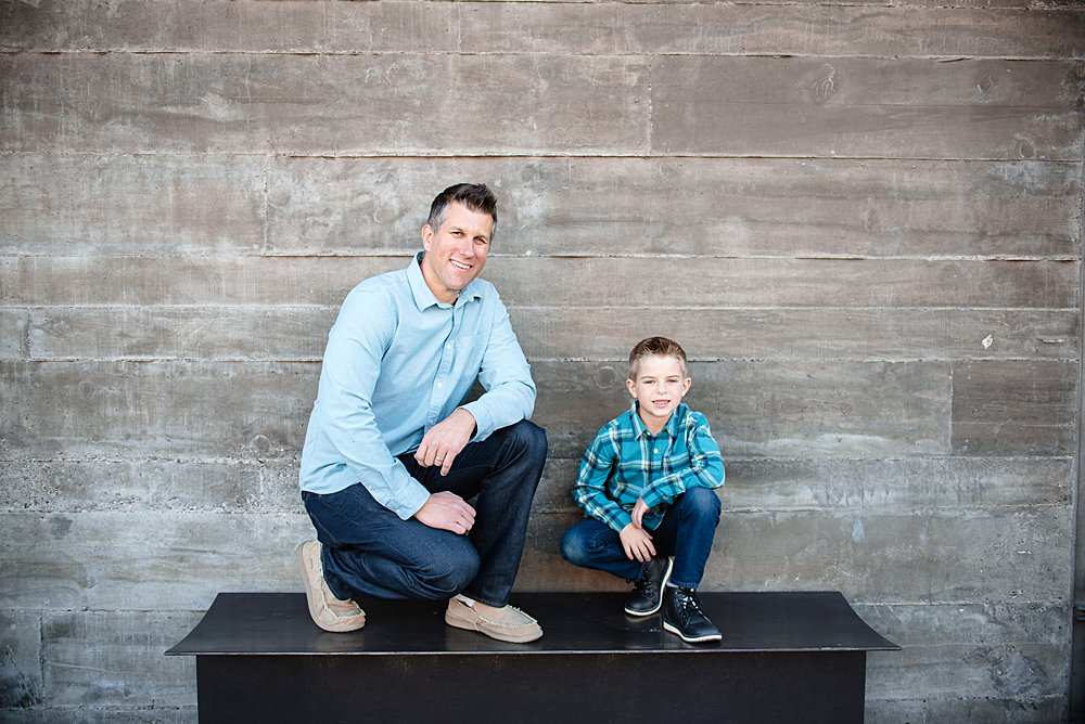 A boy and his dad pose on a bench in front of a stone wall in Bend Oregon