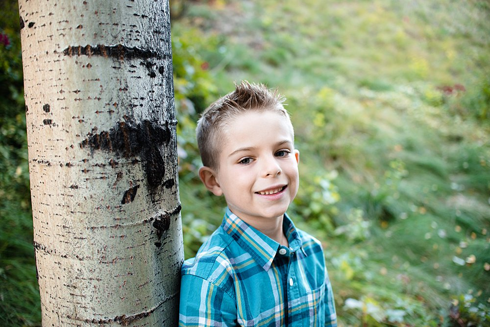 Boy poses next to an aspen tree in the Old Mill District in Bend