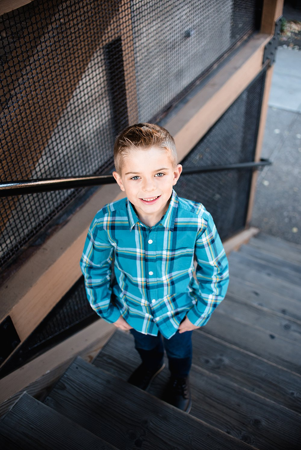 a boy poses on stairs in the Old Mill District