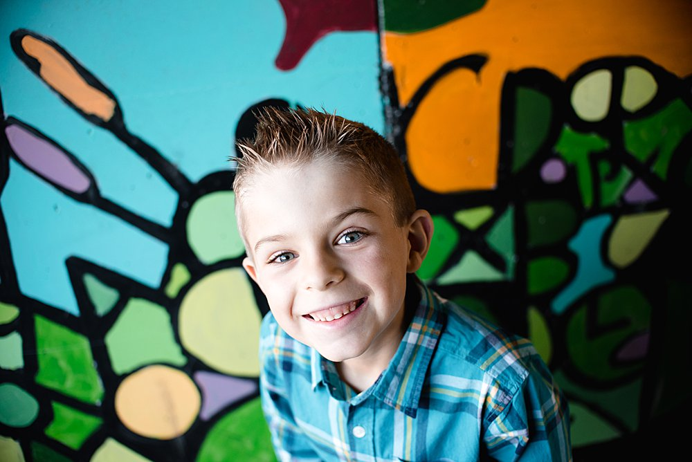 close up of a young boy smiling at the camera in front of a colorful tunnel in the Old Mill District