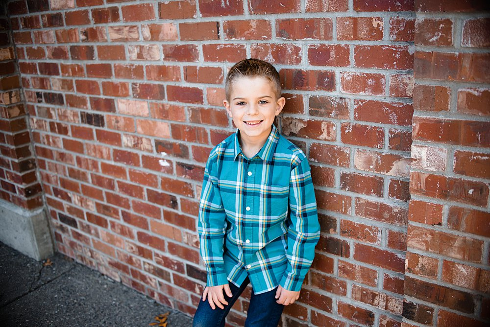 a close up of a boy posing in front of a brick wall in Bend Oregon