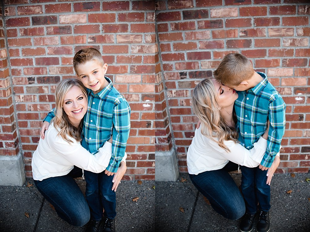 mother and son embrace in front of a brick wall in the Old Mill District in Bend