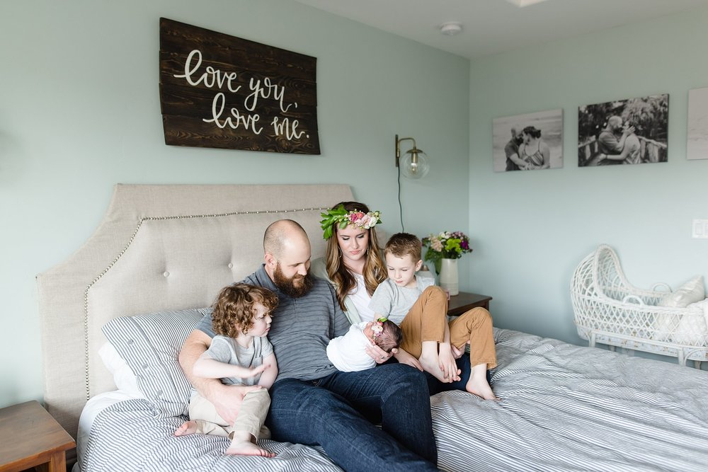 family lays on bed gazing at their new baby girl