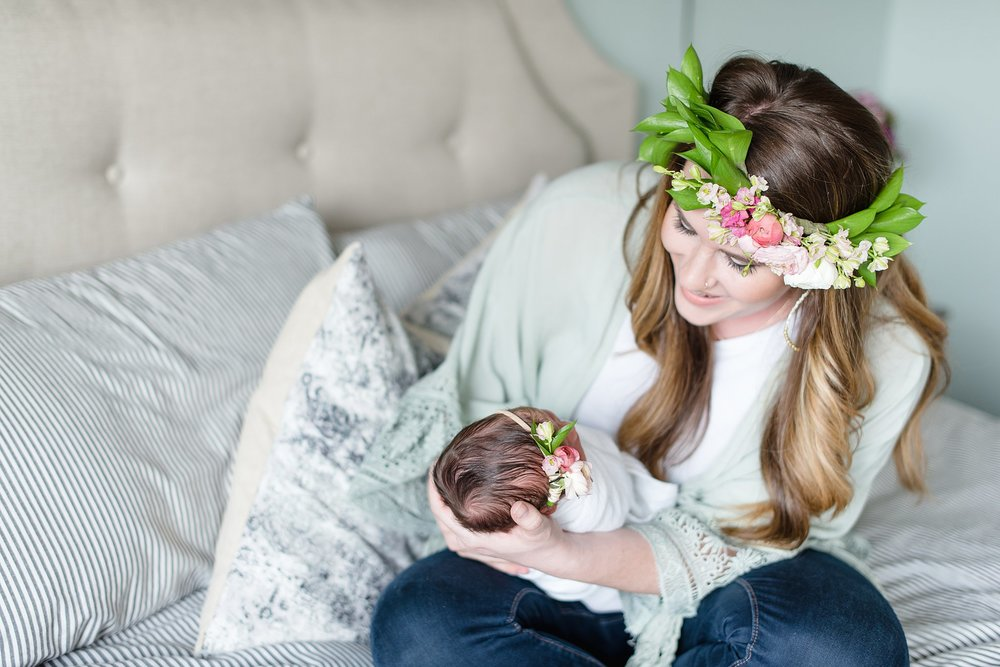 a mother wearing a flower crown smiles at her new baby