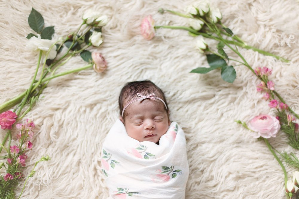 baby girl is surrounded by flowers as she sleeps