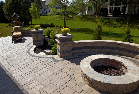 A lovely patio are with a retaining wall and fire pit.Photo Credit UniLock