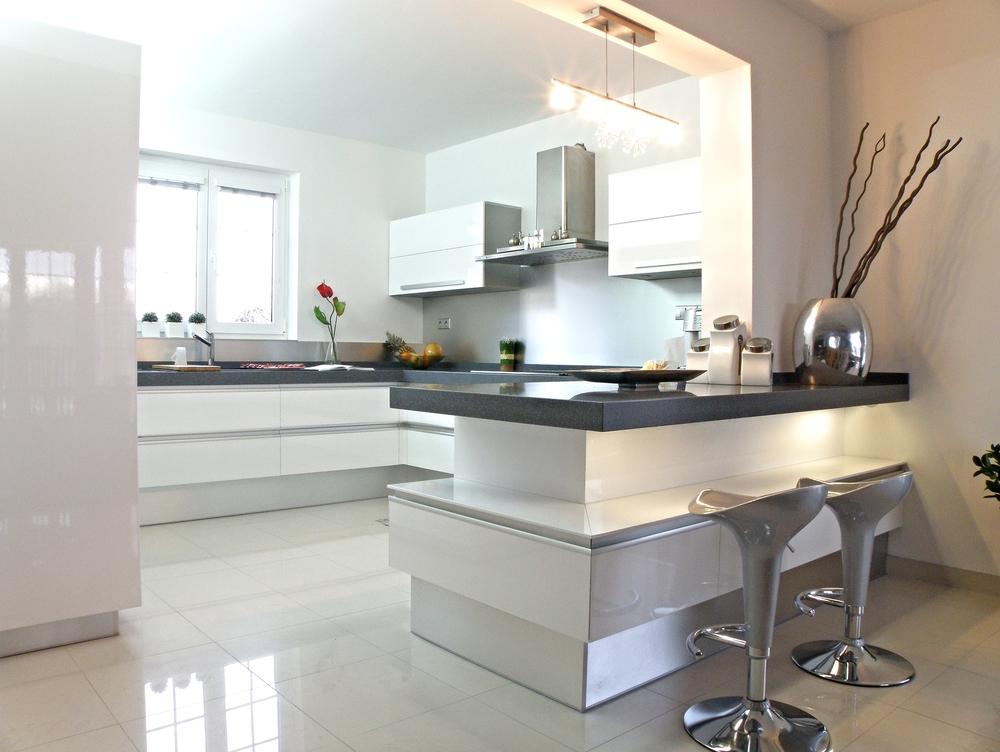 Bílá kuchyně je ztělesněním čistoty a klidu. Šedé odstíny pracovních desek spolu s bílými plochami působí velmi esteticky a nerez doplňky se do této moderní kuchyně skvěle hodí. A mimochodem - úklid lesklé kuchyně je překvapivě jednodušší, než byste si mysleli.