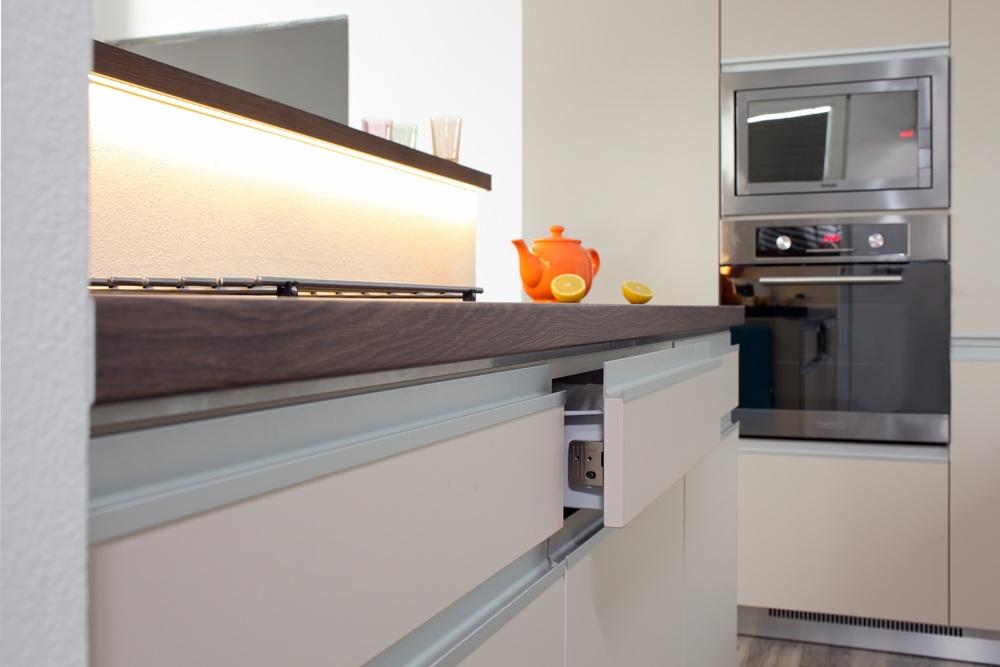Když se řekne zásuvka, tak si polovina lidí představí elektrickou zásuvku a proto se zásuvky v kuchyni nazývají výsuvy. Ať to nazveme jakkoli, jedna věc je jasná, jedná se o prvek každé praktické kuchyně. Jakmile výsuvy navrhne i zkušený designer kuchyní, mají z toho dokonalý užitek i uživatelé. Horizontální linie zásuvek je podtržena použitými eloxovanými profily. Je to řešení, které kuchyňský ostrůvek opticky prodlužuje a spolu s kovovým soklem působí elegantně. Kovový povrch je doplněn nerezovými spotřebiči. Elektrická trouba ve výši pasu a mikrovlnná trouba v úrovni očí je z ergonomického hlediska příkladně navržená. Mezi dvěmi vysokými skříněmi působí tento tandem spotřebičů velmi vyváženě a symetricky. Toto řešení je velice oblíbené u klientů, kteří si s námi novou kuchyň realizují.
