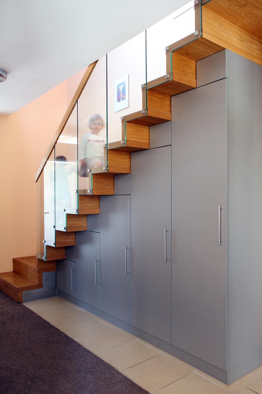 Ukázka toho, jak elegantně lze vytvořit úložné prostory pod schodištěm, maximálně je využít a vyhnout se tak komplikovanému řešení z betonu a ocelové výztuže. Skříně tvoří nosnou konstrukci pro nášlapy dřevěných schodů - typicky jde o prvek, do kterého se vyplatí investovat čas a promyslet jej do všech detailů. Vše je doprovázeno skleněným zábradlím s důrazem na design, praktičnost a také bezpečí vašich dětí.