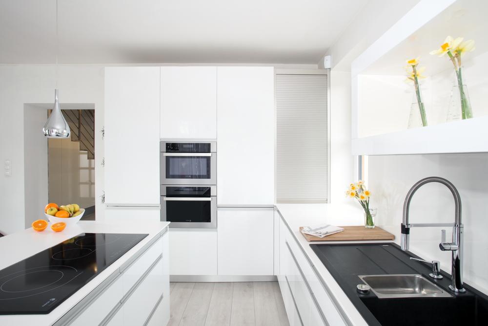 Bílá elegance. Čistota. Otevřený prostor a světlo. Tak všechno tohle se dá říci o bílých kuchyních. Pakliže k tomu přibude správná kombinace úchytové profily a čela v bílém lesku, pracovní deska z umělého kamene, tak se dá očekávat krásná kuchyň. Výsledný efekt dokáží umocnit správně vybrané kuchyňské spotřebiče. Netradičně tvarovaná indukční varná deska s varnými zónami vedle sebe s černým sklokeramickým povrchem a černý granitový dřez, naproti desky, působí vskutku harmonickým dojmem. V této kuchyni je všechno poruce.