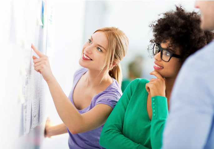 two women looking at whiteboard.jpg
