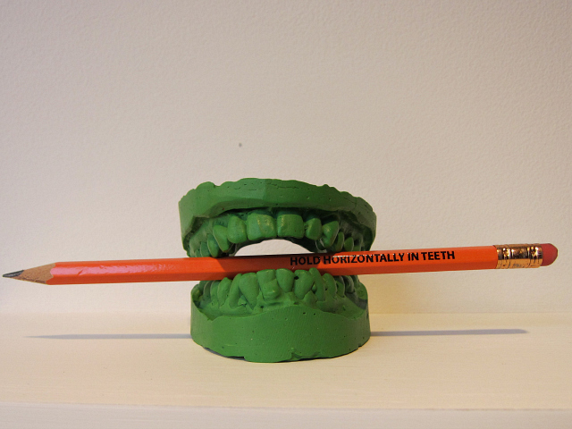 """Green Teeth"" by  Alix Lambert  (MFA AP Faculty) is included in the SPRING/BREAK room curated by Angela Conant.      ""Entering the room curated by Angela Conant the theme of pencils immediately jumps out, but how exactly they work into all the art isn't evident until you read further and find that Conant is playing off a 1998 experiment that asked subjects to keep pencils between their teeth while reading funny statements, discovering that they found them more funny with the pencils than without (the pencils triggering smiling muscles).""         Hyperallergic reviews SPRING/BREAK , including a room curated by Art Practice Participant  Angela Conant  (MFA AP13)."