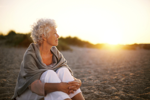 Mid-life (maga) woman sitting on a sandy beach with the sun seting looking off into the distance. Retirement coaching, creativity coaching, care-giver coaching, grief coaching all point to the topcs at hand — How can I manage all the complexities at hand? What is deeply meaningful to me now?