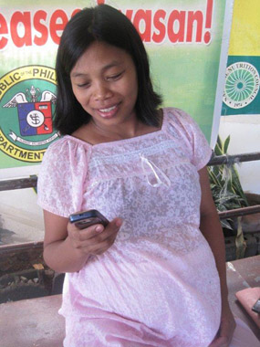 An expectant mother checks her phone. Molave Development sent 11,000 SMS with safe motherhood information. Credit: Molave Development