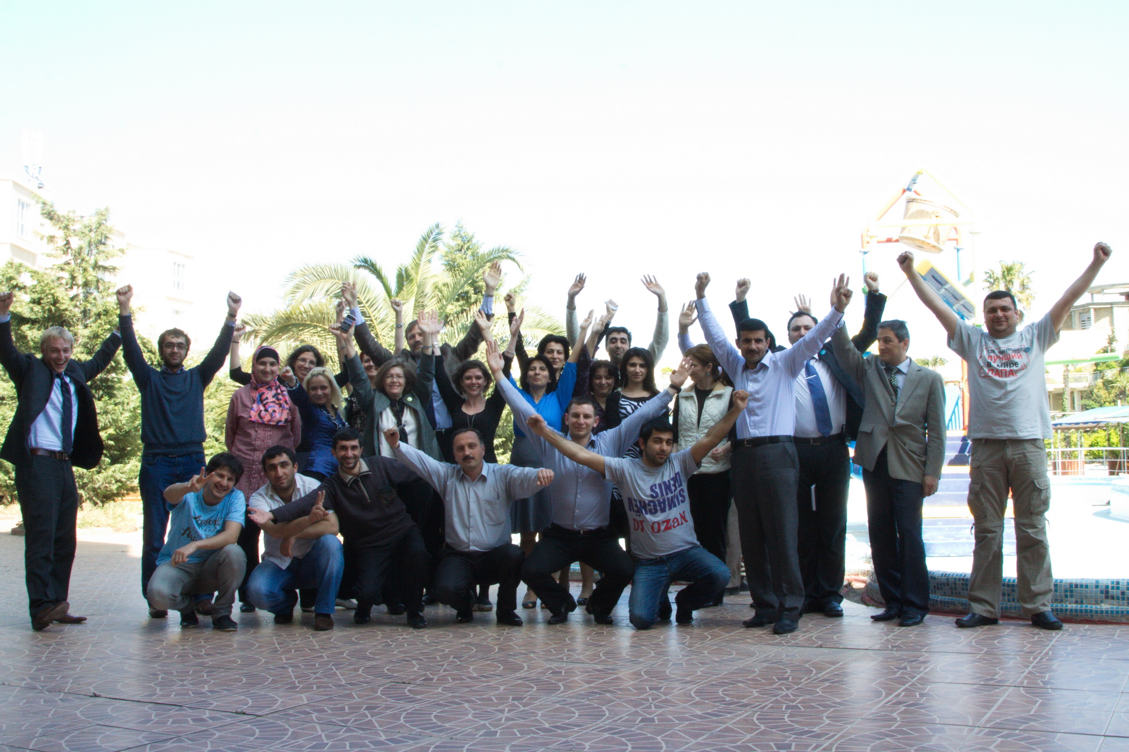 Sean (far left) and Laura (center, in black top) 'doing' the FrontlineSMS logo at a training in Azerbaijan. Photo credit: Vugar Naghiyev/USAID Azerbaijan
