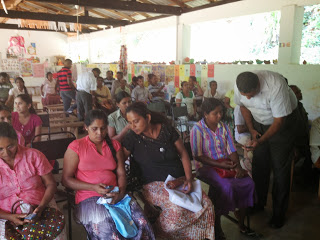 Nuwan assists participants with text messaging during a rapid prototyping exercise in Melisiripura