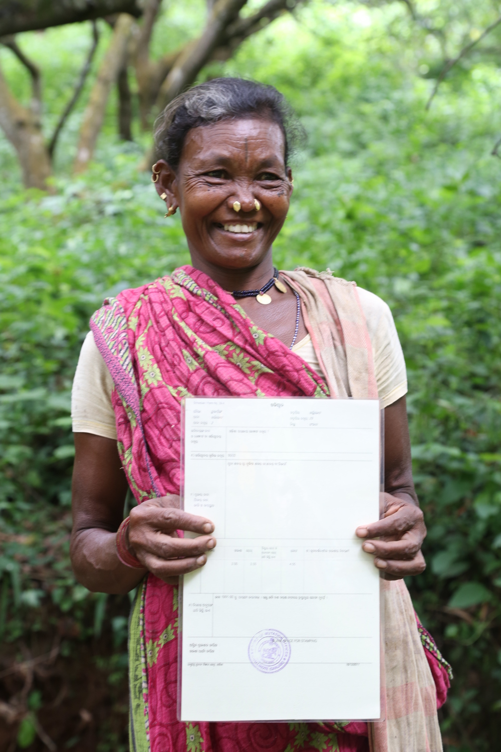A widow holds her land title in Pune, India (credit: Landesa)
