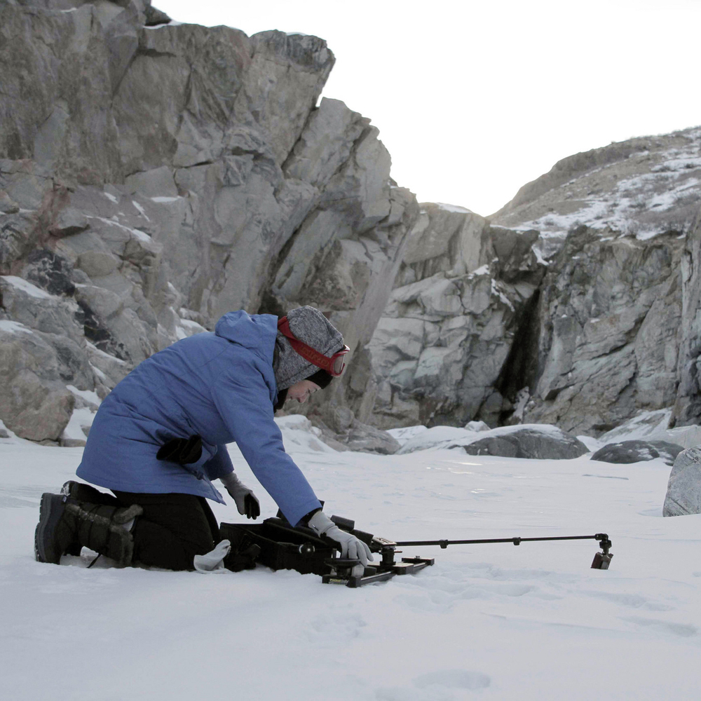 NASA Cinematographer Nasreen Alkhateeb setting up gear on frozen waterfall in Greenland