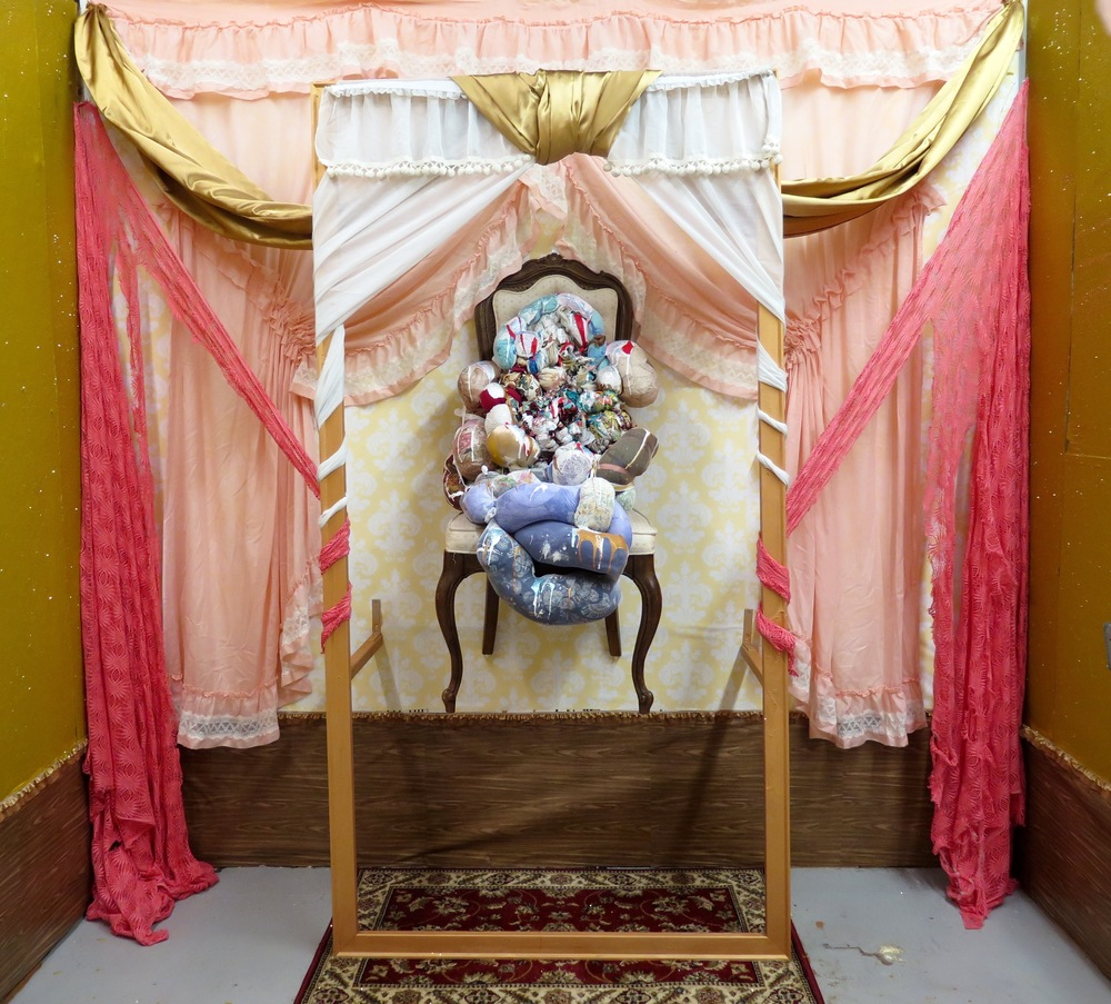 "2016,  Relic   Studio installation. Repurposed chair,  Hang In There  sculpture, synthetic silk fabric, lace, repurposed curtains, 88""x44"" stretcher bar frame, faux-wood adhesive contact paper, frilly lace trim, damask contact wallpaper, ""baby diarrhea"" house paint, gold glitter"