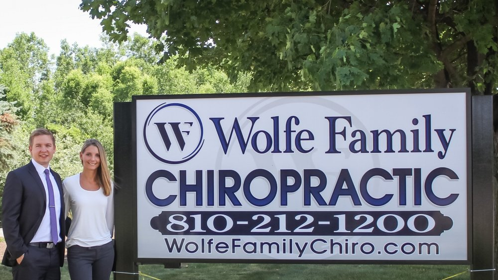 Dr. Alex Wolfe and Dr. Hannah Mikulich by the Wolfe Family Chiropractic sign on Dryden Rd. in Metamora, MI