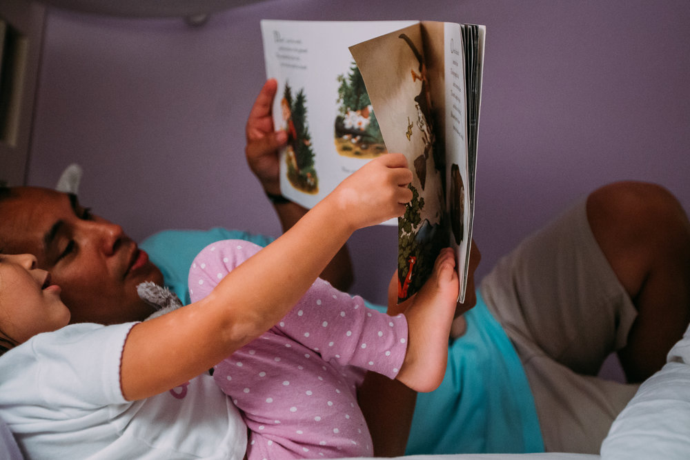 Little girl putting her foot in her book
