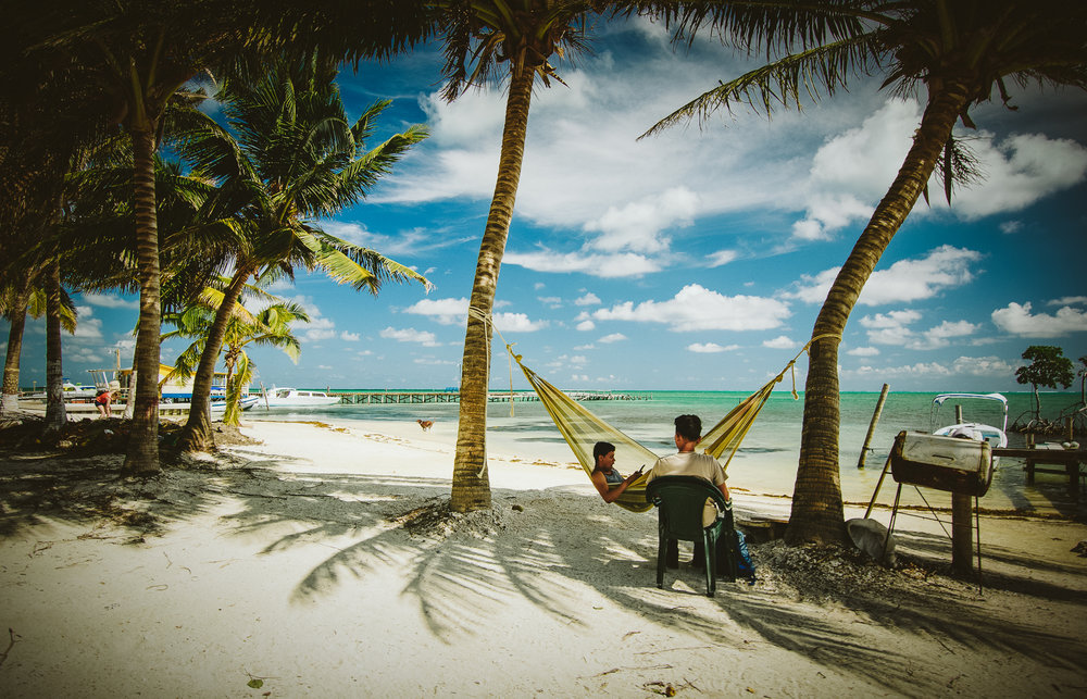 Locals relaxing in the heat of the day on Caye Caulker. Hammocks are a way of life.
