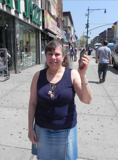 Sunset Park BID Executive Director Renee Giordano, standing on Fifth Avenue and 51st Street, says her Smartphone will be able pick up a WiFi signal on the street, thanks to the new technology upgrade. Eagle photo by Paula Katinas