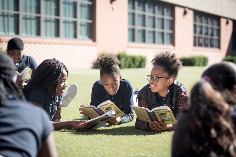 Current Amistad Academy Middle Students enjoying a day of reading on the lawn.