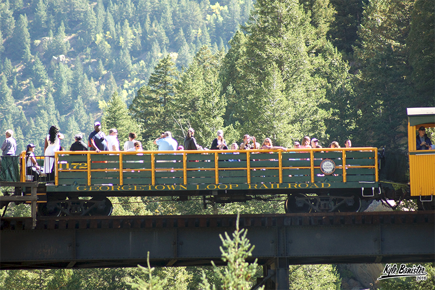 A photo of train riders enjoying the coach section train car. During the summer, it is open for people to enjoy the beautiful weather of the Rocky Mountains in historic Georgetown, Colorado. During the winter, the Georgetown Loop Railroad covers the coach section to keep passengers nice and warm. A great train car for families or larger groups.