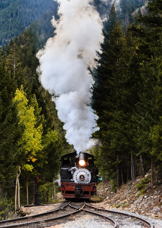 A photo of the Shay Number nine steam engine rolling down the tracks at the Georgetown Loop. Steam spouts from the top in this beautiful vertical photo.