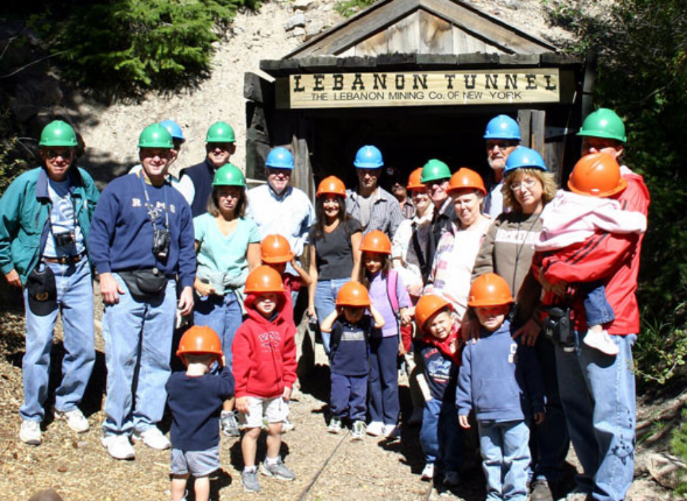 A picture of a group of Georgetown Loop train riders in front of the Lebanon tunnel, about to take a mining tour in the historic mine in Georgetown, Colorado.