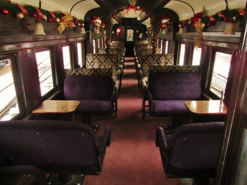 A photo of the inside of the Waldorf car, featuring tables and purple velvet seats. A beautifully decorated parlor car. The Georgetown Loop Railroad is proud to run this beautiful car.