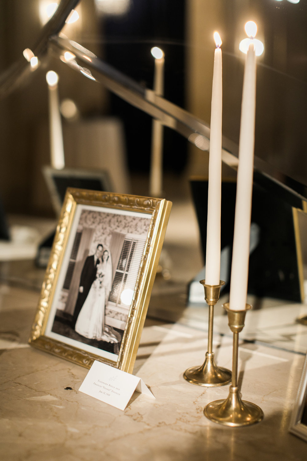 Framed family wedding photos with taper candles at Plaza wedding