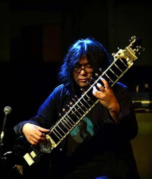 ヨシダダイキチ 1996年からインドにてシタールとインド音楽を学ぶ。世界的に活躍するウスタッド・シュジャート・カーン/ustad shujaat khanに師事。 YOSHIMI(ボアダムス/ooioo)とのユニット「saicobaba」を結成し5枚のCDをリリース。 様々なアジア楽器のポリリズムと歌唱法を取り入れた「AlayaVijana」を結成し5枚のCDをリリース。シタール5~30台を使ったユニット「sitaar tah!」を結成しニューヨークachiverecord/importantrecordより2枚のCDをリリース。 日本のレーベルからオリジナルアルバム「Tah!」をリリース。UAのアルバム「ファティマとセミラ」「テュリ」を楽曲提供、プロデュース。 奄美民謡の朝崎郁恵のアルバム「はまさき」を、インド楽器、バリ・ガムランなど多彩なアジア音楽でアレンジしたアルバムをプロデュース。