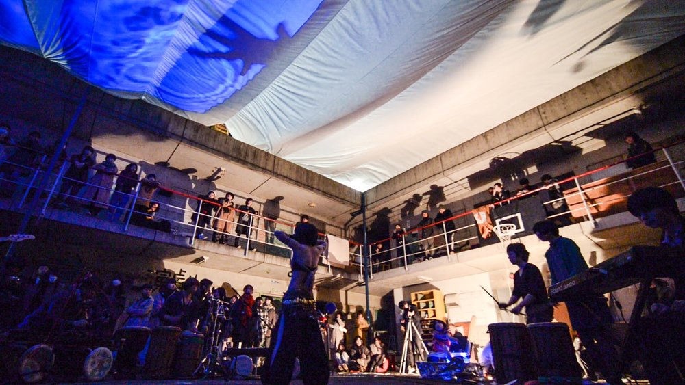 都会民族楽団 panorama   炎・水・光・映像・身体を巧みに使い、ライブ空間を自在に変容させる異色の楽団。 過去のパフォーマンスでは、吹き抜けのコンクリート建築を200㎡の巨大な布で覆う会場設計や、オリジナルの照明装置「水ジェクション」を使用した。他に類を見ない演出と執拗なまでのDIY精神が反響を呼んでいる。   http://panorama-live.tumblr.com