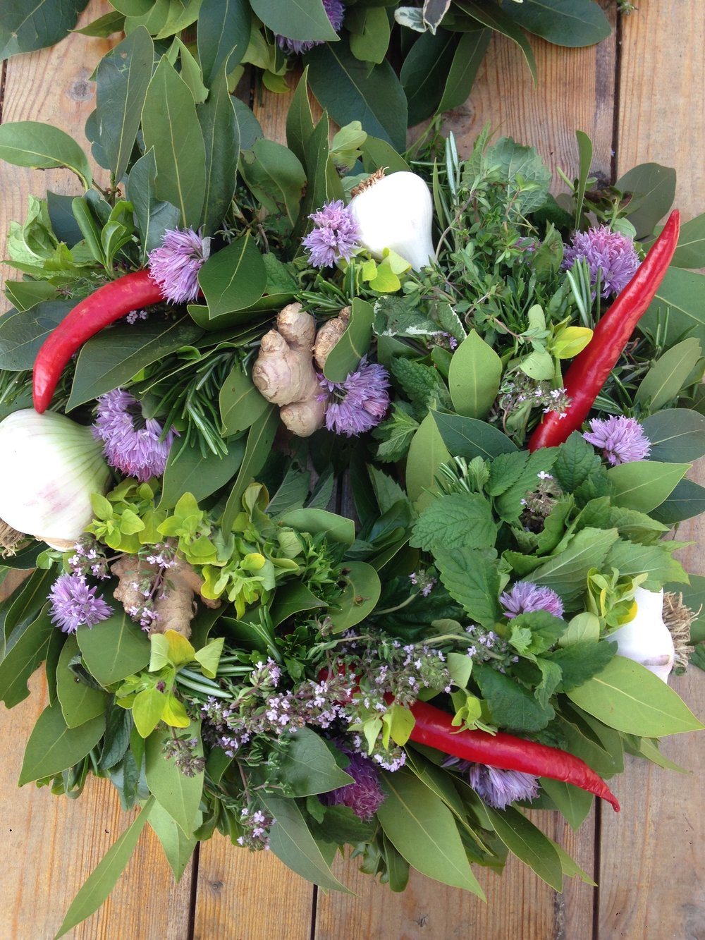 Fresh herb wreath with chili, bay leaf, rosemary, mint, ginger, garlic, thyme, chives, marjoram and sage.