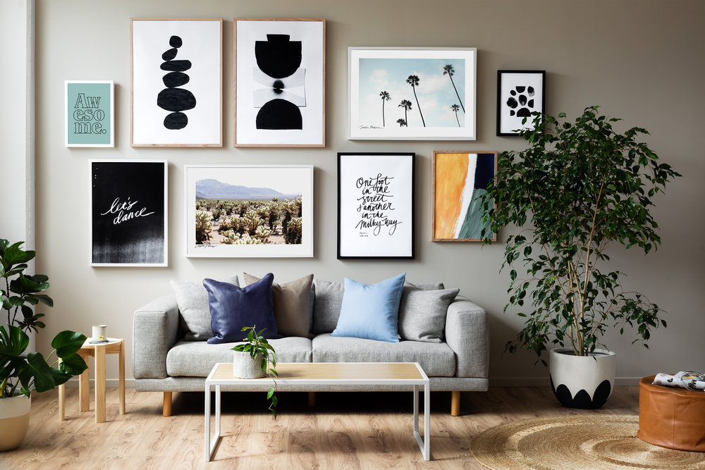 The tan, blue, green, black and white in the prints and frames are repeated in the artwork and across the room in cushions, vases, plants and the footstool.  Image: Prints by Hunting for George