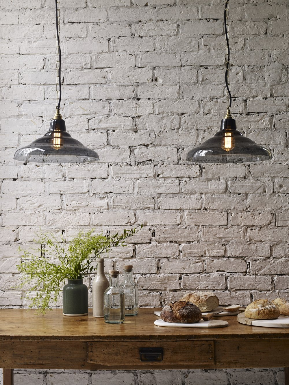 Hanging pendants low above a dining room table means that the light isn't blocked by people, and so no shadows are cast. Use dimmer switches to keep the light soft and ambient. Image via Davey Lighting.