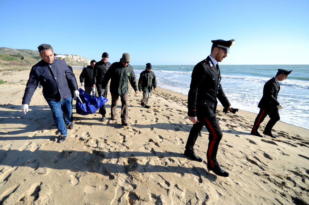 People carry a bag containing the dead body of a drowned migrant on the Sicilian beach of Siculiana, Western Sicily, Italy February 19, 2016. REUTERS/Guglielmo Mangiapane