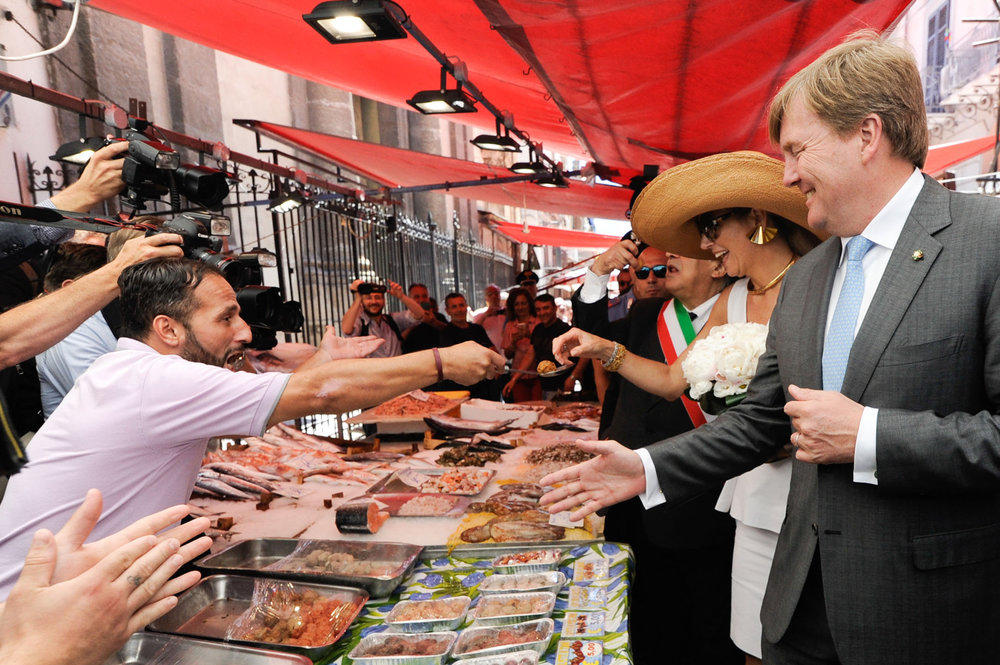 A street vendor offers a swordfish meatball to King Willem Alexander and his wife Queen Maxima of the Netherlands during their trip to Palermo, southern Italy June 21, 2017. LAPRESSE/Guglielmo Mangiapane