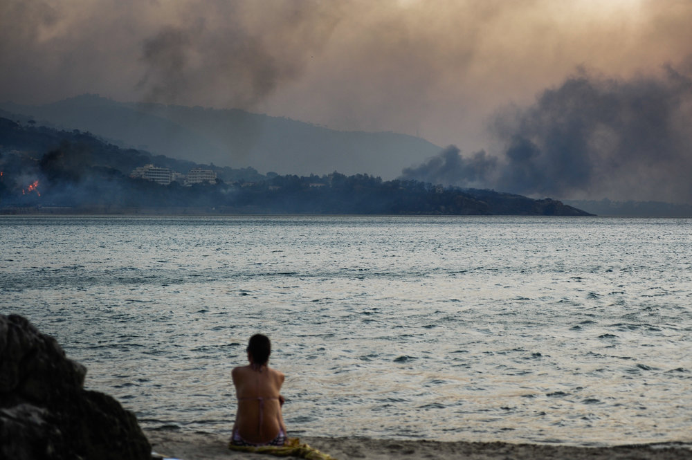 A woman sits on the beach as fires break out in Cefalù, near Palermo, southern Italy, June 16, 2016.